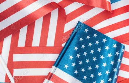 panoramic shot of american flags stacked on blue background