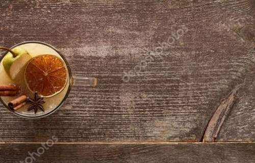 top view of warm pear mulled wine with spices and dried citrus on wooden table, panoramic shot