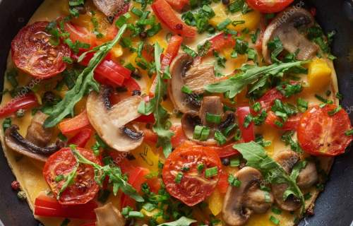 top view of homemade omelet with mushrooms, tomatoes and greens