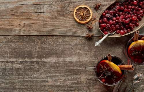 top view of red spiced mulled wine with berries, anise, orange slices and cinnamon on wooden rustic table