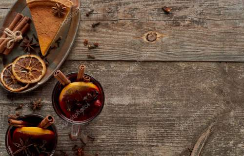 top view of piece of pie and red spiced mulled wine with berries, anise, orange slices and cinnamon on wooden rustic table