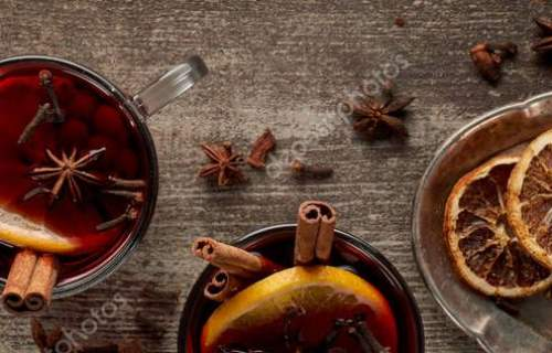 top view of red spiced mulled wine with berries, anise, orange slices and cinnamon on wooden table, panorama shot