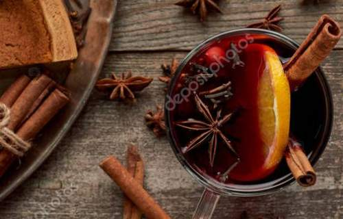 top view of red spiced mulled wine near fir branch, pie, berries, anise, orange slices and cinnamon on wooden rustic table, pano