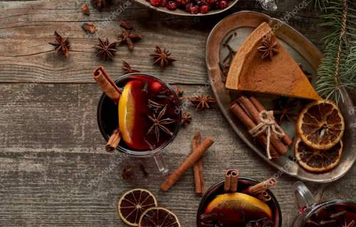 top view of red spiced mulled wine near fir branch, pie, berries, anise, orange slices and cinnamon on wooden rustic table