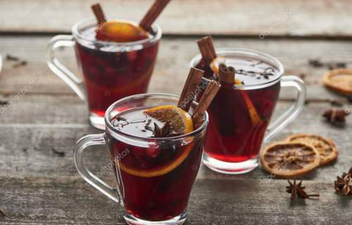 hot red spiced mulled wine with berries, anise, orange slice and cinnamon on wooden rustic table