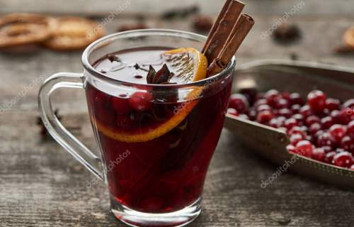 red spiced mulled wine with berries, anise, orange slice and cinnamon on wooden rustic table