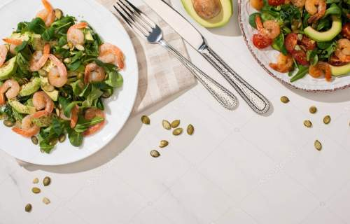 top view of fresh green salad with shrimps and avocado on plates near cutlery on white background