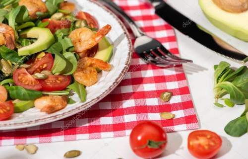close up view of fresh green salad with shrimps and avocado on plate near cutlery on plaid napkin and ingredients on white backg
