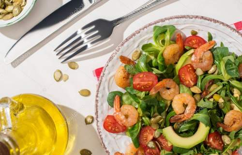 top view of fresh green salad with shrimps and avocado on plate near cutlery on plaid napkin and ingredients on white background