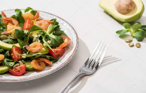 selective focus of fresh green salad with shrimps and avocado on plate near fork and ingredients on white background
