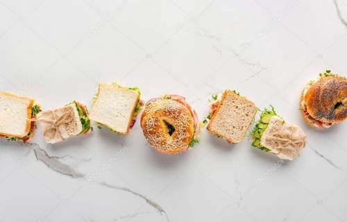 flat lay with fresh sandwiches and bagels on marble white surface