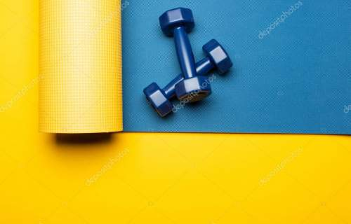 top view of blue fitness mat with dumbbells on yellow background