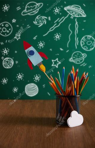 colorful pencils, rocket, cloud sign on wooden table with chalkboard on background with universe icons