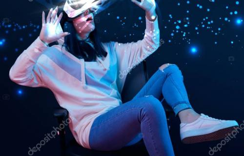 young shocked woman in virtual reality headset sitting on chair and gesturing among glowing data illustration on dark background