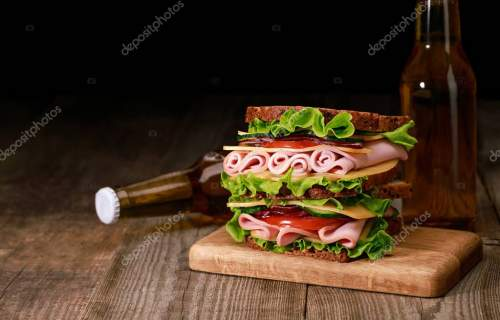 fresh sandwich with lettuce, ham, cheese, bacon and tomato on wooden cutting board near bottles of beer isolated on black