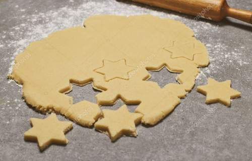 Baking Christmas Gingerbread cookies. Stars on grey stone table. Christmas and New year food. Preparing for Christmas, cooking.