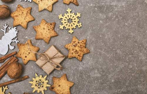 Christmas Holiday Background with Gingerbread cookies with decoration. Cinnamon, nuts, golden snowflakes on grey table. Copy spa