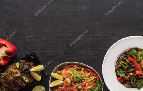 top view of delicious spicy thai noodles on wooden grey surface
