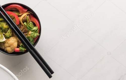 top view of delicious meat and vegetable thai noodles with chopsticks on marble grey surface, panoramic shot