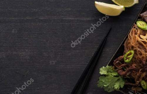 top view of meat thai noodles near chopsticks, lime and paprika on wooden grey surface, panoramic shot