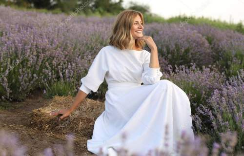 side view of attractive woman in white dress sitting in purple lavender field and looking away