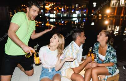 Young couples holding beer bottles outdoors at night