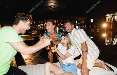 Selective focus of excited young people clinking with beer near swimming pool at night