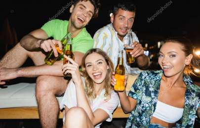 Selective focus of young women holding bottles of beer near boyfriends outdoors at night