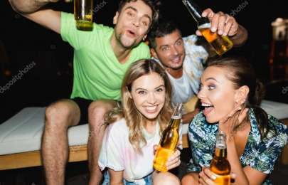 Selective focus of excited young friends holding bottles of beer during party at night