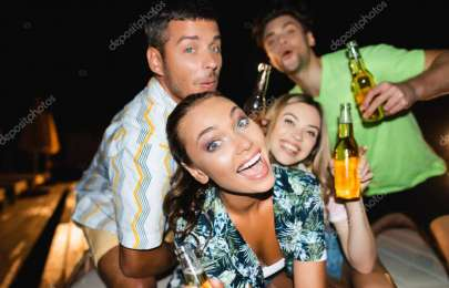 Selective focus of woman looking at camera near boyfriend and friends at night