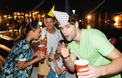 Selective focus of young man in party cap pointing with finger at camera near friends with beer outdoors at night