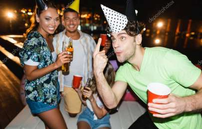 Selective focus of man with disposable cup pointing at party cap near friends with beer at night