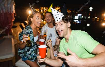 Selective focus of man in party cap pointing at disposable cup beside friends at night