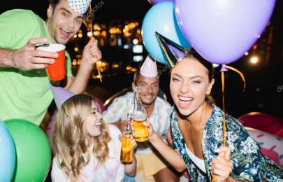Selective focus of woman holding beer bottle and balloon during party with friends at night