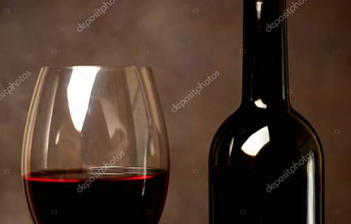 Wine glass with red wine and bottle against a stone background.