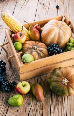 Autumn vegetables and fruits in a box on a wooden background